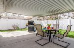 Large covered back patio with outdoor dining space and a BBQ