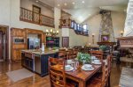 Kitchen on Main Level. Gorgeous rock fireplace, two dining tables, large granite bar, and deluxe appliances