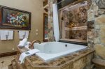 Master Suite Bathroom with stunning marble and stone floors and shower, jetted roman tub