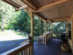 The covered front porch looks out toward a fire pit and picnic table