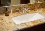 The guest bathroom features refined, granite countertops