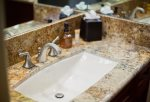 The bathroom features granite counter tops and custom wood cabinets