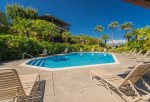 Palm tress and floral plumeria trees line the pool grounds