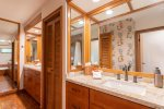 A large, remodeled bathroom features new his-and-her vanities with custom cabinets, a full-length mirror and newly refinished oversized soaking tub