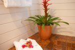 Vintage Maui orange clay tile floors and festive pineapple wallpaper adorn the master bathroom
