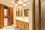 Guest bathroom features shower, sink, toilet, washer/dryer and large closet