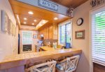 The breakfast bar opens to kitchen and is the perfect spot for morning pancakes and Kona coffee