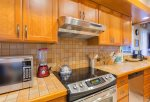 The kitchen features custom cabinets and stainless steel appliances