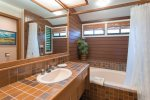 The bathroom features an oversized soaking tub, perfect after a long day exploring the island