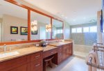 Beautiful bathroom features twin vanities, large closet, toilet and large walk-in shower