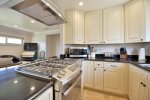 Kitchen includes a gas range, high end appliances and a breakfast bar.