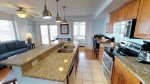 Modern kitchen with stainless steel appliances, glass top range, granite counter tops and island with seating for meals