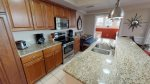 Gorgeous kitchen with stainless steel appliances, glass top range, granite counter tops, and Bistro table