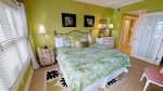 Master bedroom with king bed, flat panel TV and adjoining bathroom