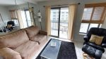 Comfortable living room with queen sized sofa sleeper, flat screen TV, and patio access