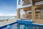 Master bedroom with views of the water, accompanied with a furnished balcony.