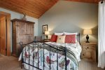 Master bedroom with queen bed and attached bath at Cove Beach Lodge