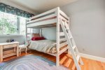 Upstairs bedroom with twin bed and bunk beds at Ocean Villa