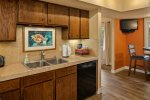 The kitchen is fully equipped with a side by side fridge and glass top stove