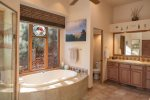 The master bathroom is spacious with a large tub and walk-in shower
