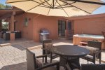 A view of the patio with outdoor dining table, BBQ grill, private hot tub and patio furniture