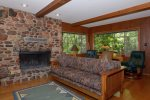 The living area has a large stone clad wood burning fireplace
