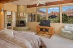 A luxurious bedroom with a kiva fireplace, flat screen TV and more red rock views from your pillow