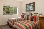 Bedroom 3 has two twin beds and looks out onto Sedona`s lush landscapes
