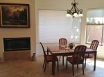 Dining table with 4 seats, next to gas fireplace