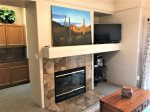 The living area features a cozy gas fireplace and flat screen TV for entertainment