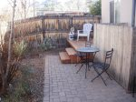 The fenced back-yard has outdoor seating and a BBQ grill