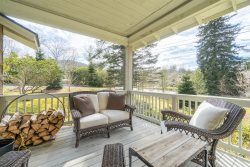 Lounge on the beautiful front porch in this tastefully decorated home just minutes from downtown and right across the street from Harris Lake.