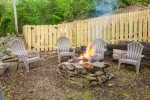 Side yard fire pit behind fenced pet area