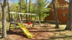 Playground and grilling area next door to this Waterville Estates Rental