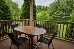Deck with table overlooking beautifully landscaped lawn