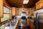 The kitchen has nice stainless appliances and is stocked with dishes, glassware, and utensils