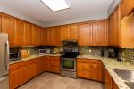 The large kitchen boasts quality stainless appliances and is stocked with dishes, glassware, and utensils.