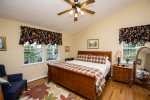 Nice King master bedroom with ceiling fan, mirror, dresser and end table.