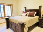 Basement bedroom with queen bed and attached bathroom access