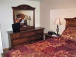 Just off the living room, the main bedroom has a pillow top queen bed and matching vanity dresser.