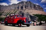 Take a red bus tour in Glacier national park.