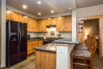 Kitchen with granite counters, stainless appliances, and extra bar seating