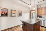 Open kitchen has stunning granite countertops and stainless steel appliances.
