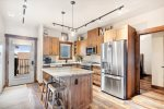 Open kitchen with modern decor, lots of cabinet space. Very charming.