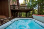 The hot tub is on its own deck perched in the forest