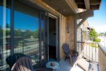 Sliding glass door from living space onto relaxing balcony.