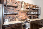 Open kitchen has stunning concrete countertops, and brick backsplash.