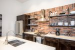 Open kitchen has stunning concrete counter tops, and brick backsplash.