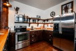 Stainless steel appliances and open shelves  add contemporary flair