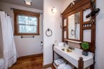 The guest bath with antique sink and tub/shower combo